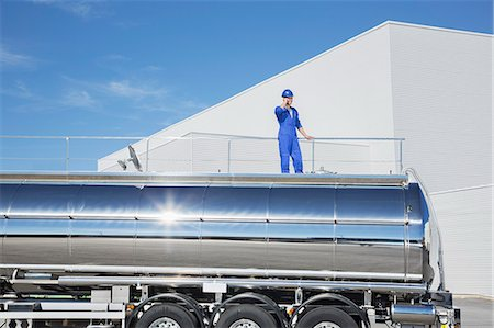 Worker talking on cell phone on platform above stainless steel milk tanker Stock Photo - Premium Royalty-Free, Code: 6113-07565399