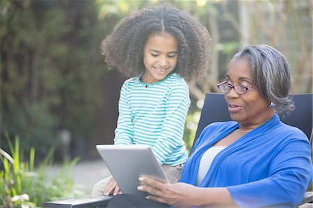 domestic - Grandmother and granddaughter using digital tablet outdoors Stock Photo - Premium Royalty-Free, Code: 6113-07565463