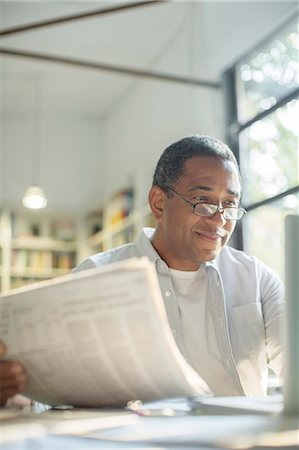 domestic life - Senior man reading newspaper and using laptop Stock Photo - Premium Royalty-Free, Code: 6113-07565478