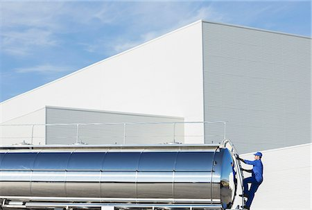 side view tractor trailer truck - Worker climbing ladder at back of stainless steel milk tanker Stock Photo - Premium Royalty-Free, Code: 6113-07565403