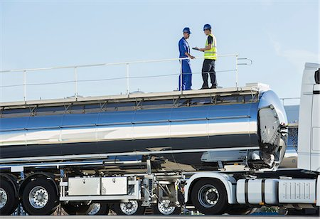 side view tractor trailer truck - Workers on platform above stainless steel milk tanker Stock Photo - Premium Royalty-Free, Code: 6113-07565404