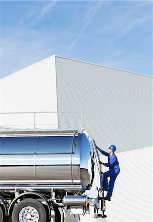 side view tractor trailer truck - Worker climbing ladder at back of stainless steel milk tanker Stock Photo - Premium Royalty-Free, Code: 6113-07565408
