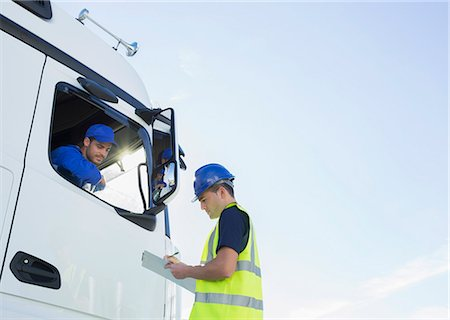 Worker with clipboard talking to truck driver Stock Photo - Premium Royalty-Free, Code: 6113-07565425