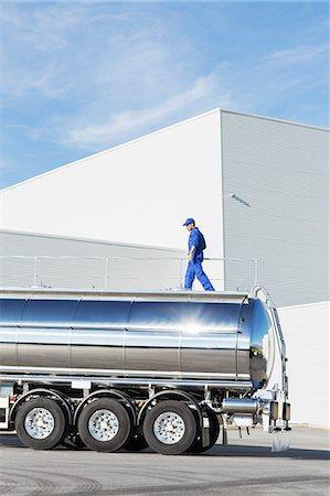 side view tractor trailer truck - Worker walking on platform above stainless steel milk tanker Stock Photo - Premium Royalty-Free, Code: 6113-07565431