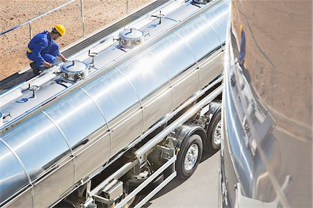 side view tractor trailer truck - Worker on platform above stainless steel milk tanker Stock Photo - Premium Royalty-Free, Code: 6113-07565437
