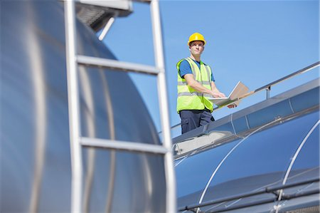 side view tractor trailer truck - Worker using laptop on platform above stainless steel milk tanker Stock Photo - Premium Royalty-Free, Code: 6113-07565438