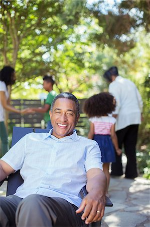 Portrait of smiling senior man on patio with family in background Stock Photo - Premium Royalty-Free, Code: 6113-07565542