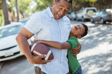 family  fun  outside - Grandson tackling grandfather with football Stock Photo - Premium Royalty-Free, Code: 6113-07565559