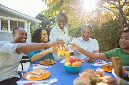 Happy family toasting juice glasses at patio table Stock Photo - Premium Royalty-Free, Code: 6113-07565572