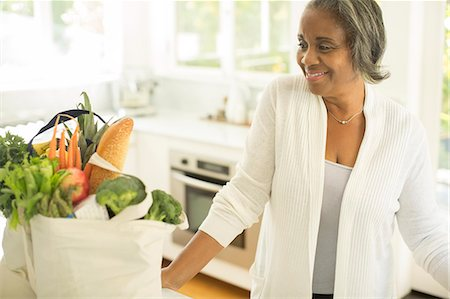 Smiling senior women with groceries in kitchen Stock Photo - Premium Royalty-Free, Code: 6113-07565531