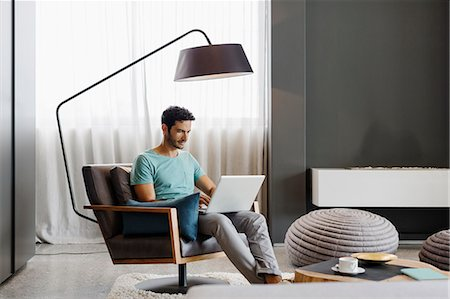 Man using laptop in living room Stock Photo - Premium Royalty-Free, Code: 6113-07565690
