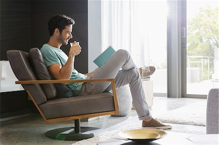 Man drinking tea and reading book in living room Stock Photo - Premium Royalty-Free, Code: 6113-07565694