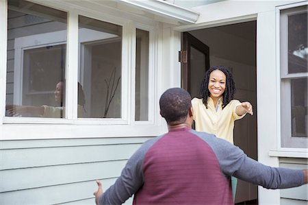 Enthusiastic woman greeting man in doorway Stock Photo - Premium Royalty-Free, Code: 6113-07565601