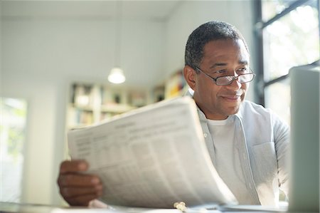 Senior man with newspaper using laptop Stock Photo - Premium Royalty-Free, Code: 6113-07565608