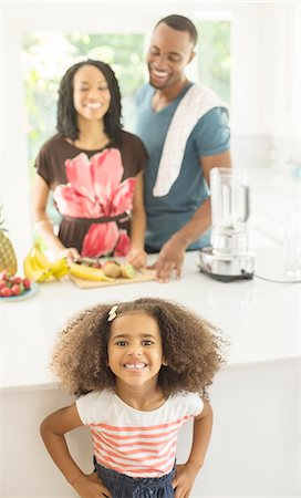 Portrait of enthusiastic girl in kitchen with parents in background Stock Photo - Premium Royalty-Free, Code: 6113-07565613