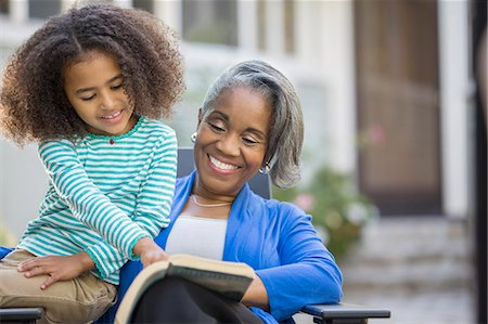 Grandmother and granddaughter reading book on patio Stock Photo - Premium Royalty-Free, Code: 6113-07565612