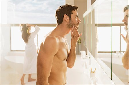 Man checking beard in bathroom mirror Stock Photo - Premium Royalty-Free, Code: 6113-07565759