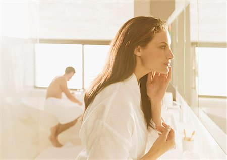 Woman looking at face in mirror Stock Photo - Premium Royalty-Free, Code: 6113-07565761