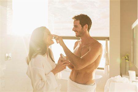 Couple playfully applying moisturizer in bathroom Stock Photo - Premium Royalty-Free, Code: 6113-07565764