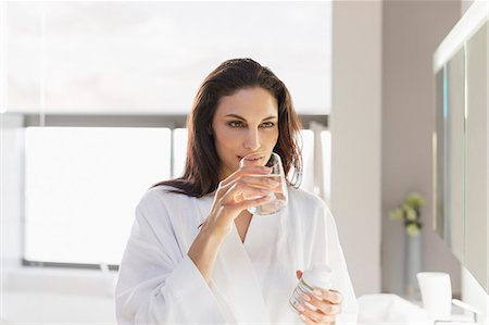 Woman taking medication with water in bathroom Stock Photo - Premium Royalty-Free, Code: 6113-07565766