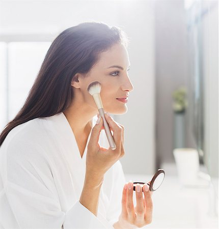 Woman in bathrobe applying makeup in bathroom Stock Photo - Premium Royalty-Free, Code: 6113-07565713