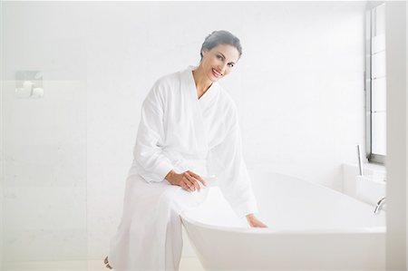 Portrait of smiling woman in bathrobe preparing bath Stock Photo - Premium Royalty-Free, Code: 6113-07565717