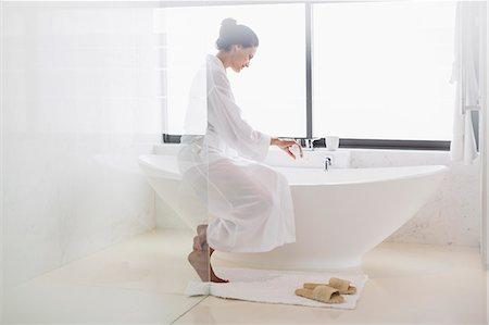 Woman in bathrobe preparing bath Stock Photo - Premium Royalty-Free, Code: 6113-07565715