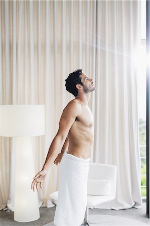 stretch - Man in towel basking in sunlight at bedroom window Stock Photo - Premium Royalty-Free, Code: 6113-07565729