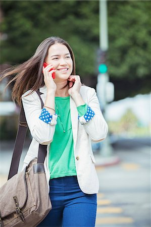 Happy businesswoman talking on cell phone in crosswalk Stock Photo - Premium Royalty-Free, Code: 6113-07565854