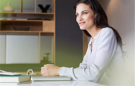 Confident woman sitting at table Stock Photo - Premium Royalty-Free, Code: 6113-07565805