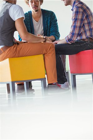 Creative business people meeting in circle on stools Stock Photo - Premium Royalty-Free, Code: 6113-07565839