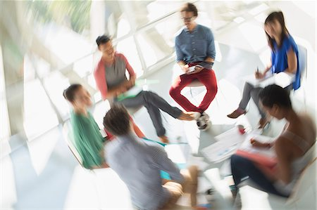 Defocused view of creative business people meeting in circle of chairs Stock Photo - Premium Royalty-Free, Code: 6113-07565957