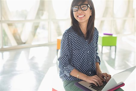 Happy casual businesswoman using laptop in sunny office Stock Photo - Premium Royalty-Free, Code: 6113-07565976