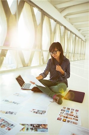 Creative businesswoman looking at photograph proofs on office floor Stock Photo - Premium Royalty-Free, Code: 6113-07565906