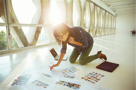 Creative businesswoman reviewing photography proofs on office floor Stock Photo - Premium Royalty-Free, Code: 6113-07565911