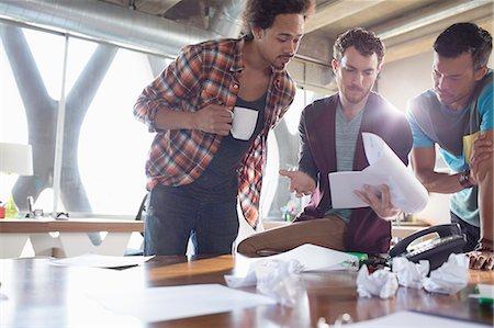 Creative businessmen reviewing paperwork in meeting Stock Photo - Premium Royalty-Free, Code: 6113-07565926