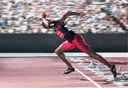 race track (people) - Sprinter taking off from starting block on track Stock Photo - Premium Royalty-Free, Code: 6113-07588649