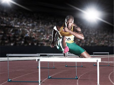 race track (people) - Runner clearing hurdle on track Stock Photo - Premium Royalty-Free, Code: 6113-07588677
