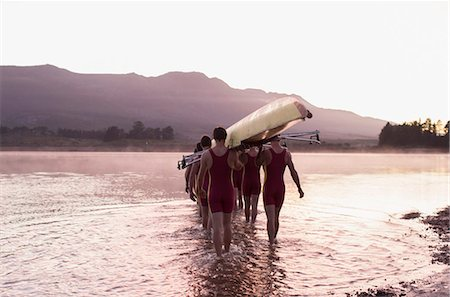 sport rowing teamwork - Rowing team carrying scull into lake Stock Photo - Premium Royalty-Free, Code: 6113-07588691