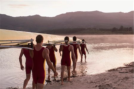 sport rowing teamwork - Rowing team carrying scull into lake at dawn Stock Photo - Premium Royalty-Free, Code: 6113-07588740