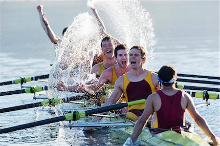 sport rowing teamwork - Rowing team splashing and celebrating in scull on lake Stock Photo - Premium Royalty-Free, Code: 6113-07588753