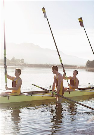 side view of person rowing in boat - Rowing team lifting oars in lake Stock Photo - Premium Royalty-Free, Code: 6113-07588790