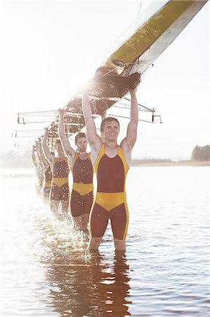 sport rowing teamwork - Rowing team carrying scull overhead in lake Stock Photo - Premium Royalty-Free, Code: 6113-07588794