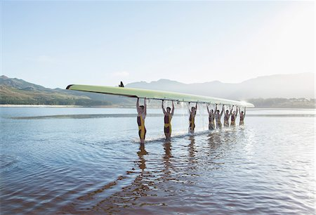 sport rowing teamwork - Rowing team holding scull overhead in lake Stock Photo - Premium Royalty-Free, Code: 6113-07588705