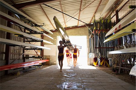 sport rowing teamwork - Rowing crew carrying scull into shed Stock Photo - Premium Royalty-Free, Code: 6113-07588728