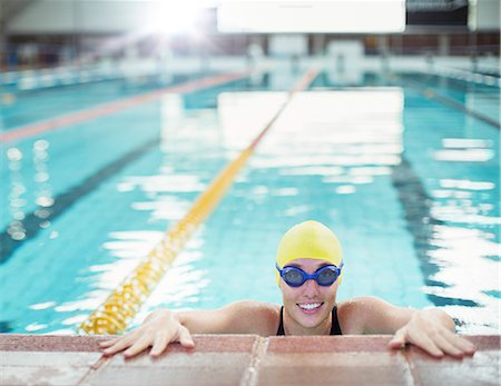 swimming - Portrait of smiling swimmer at edge of pool Stock Photo - Premium Royalty-Free, Code: 6113-07588736