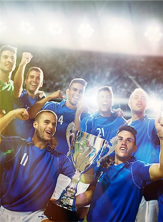 Soccer team celebrating with trophy in stadium Stock Photo - Premium Royalty-Free, Code: 6113-07588843