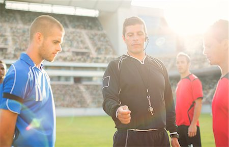 Referee tossing coin during soccer game Stock Photo - Premium Royalty-Free, Code: 6113-07588869