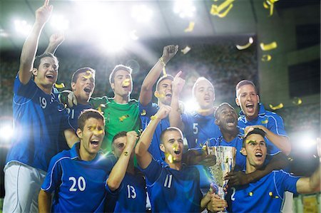 Soccer team celebrating with trophy on field Stock Photo - Premium Royalty-Free, Code: 6113-07588877