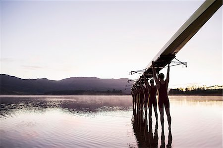sport rowing teamwork - Rowing team entering lake at dawn with scull overhead Stock Photo - Premium Royalty-Free, Code: 6113-07588807
